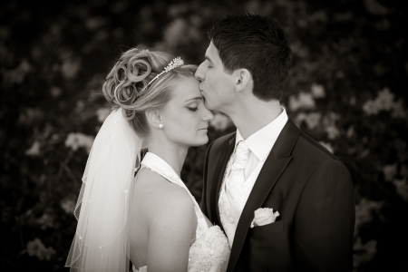 forehead: Young couple just married  groom kiss his pretty bride after the wedding ceremony  she is blond and wearing a nice diadem  classic black and white photo  no sepia