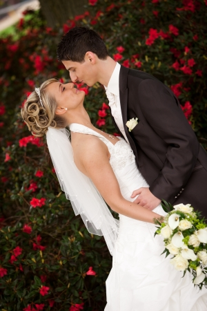 Young couple just married  groom wants to kiss his pretty bride after the wedding ceremony  she is blond and wearing a nice diadem  background red roses and foreground yellow bouquet roses Stock Photo
