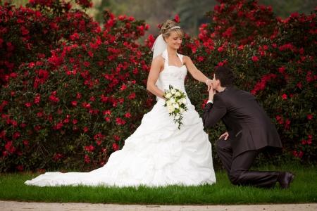 Junger Mann macht den Heiratsantrag er die Frage aller Fragen, während ihre Hand und geben einen Kuss auf die Hand natürlich, sagte sie JA zu ihm, während er kniet und schlägt