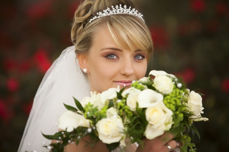 Absolute Perfect wedding portrait  Portrait of pretty attractive young bride with diadem and cute clear blue eyes and perfect skin with nice pearl earring and cute nice lips is holding the bouquet of flowers in front of her face photo