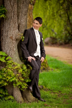 groom is standing at the tree and waiting for his bride while looking where she is  photo