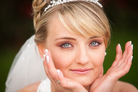 Portrait of pretty attractive young bride with diadem and cute clear blue eyes and perfect skin with nice pearl earring and cute nice lips is holding the hands beside her face photo