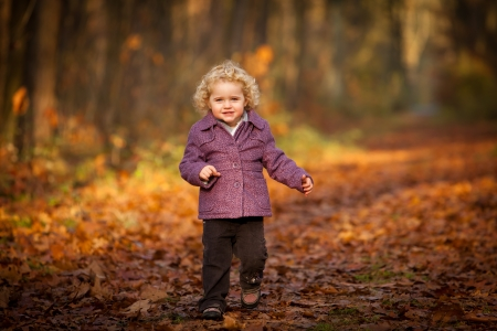 Cute curly baby running leafs Very beautiful infant baby is running through the leafs within the time of indian summer on a forest track photo