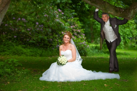 gimmick: groom is holding the branch of a big oak tree, while his bride is kneeing on the grass on a big green fresh meadow