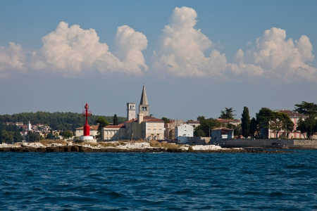 tourismus: Very nice view from the sea to Porec Nice blue and cloudy sky and clear blue water  Beacon beside the church