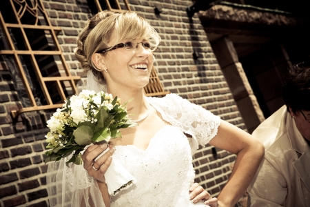 Bride with eyeglasses and sepia color is standing and holding a bunch bouquet of yellow roses photo