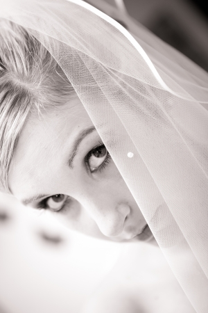 beautiful bride with cute face is directly looking in the cam while the veil is hiding a part of her face  cute eyes in this black and white photo