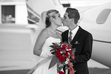 black and white wedding photo with colored bunch of red roses while holding the bouquet and kissing each other photo