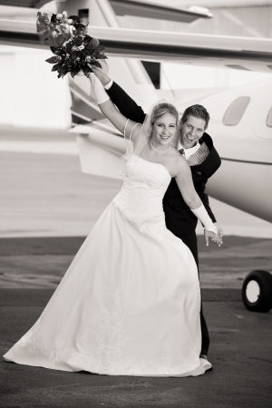 gimmick: black and white wedding photo from a very young couple at the airport with airplane in background while holding the bouquet and waggle with the arms