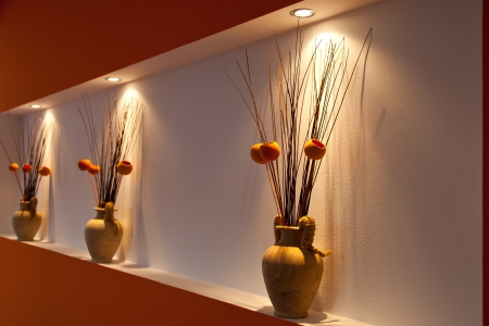 Three vases on a wall podest with warm light from above