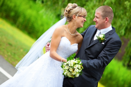 BRIDE AND GROOM LAUGHING and looking to each other while holding the yellow roses bouquet