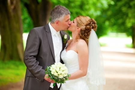 white bride with blonde hair and veil gives her groom a tender wedding kiss while holding the bouquet photo