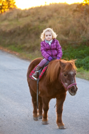 pony ride: Girl Riding a Pony - baby Ride a Horse  Lonely young cute lovely girl is riding a pretty pony horse alone  sundown in the background Stock Photo