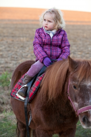 Girl Riding a Pony - baby Ride a Horse  Lonely young cute lovely girl is riding a pretty pony horse alone  sundown in the background photo