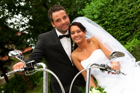 white Bride with veil and groom with bow tie are sitting on motorcycle after wedding ceremony photo