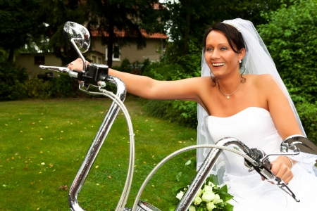 Funny bride well know as bride chick is laughing and sitting on a bike after her wedding ceremony