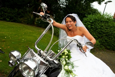 dark haired: Funny bride well know as bride chick is laughing and sitting on a bike after her wedding ceremony