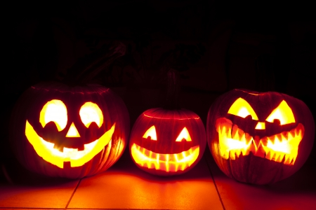 hallooween: one friendly and two scary pumpkin are shining in scary light in the dark room  three pumpkins on the floor
