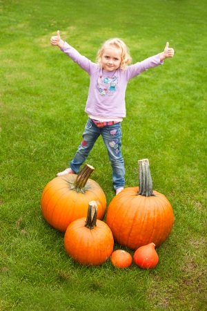 large pumpkin: Happy girl is standing on large pumpkin which she has collected and thumbs up child