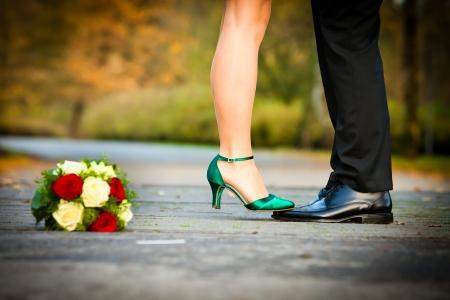 belles jambes: mariée est debout avec des chaussures de mariée vert sur palefreniers noir brillant chaussures en cuir Banque d'images