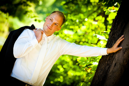 confident groom leaning against tree - groom 写真素材