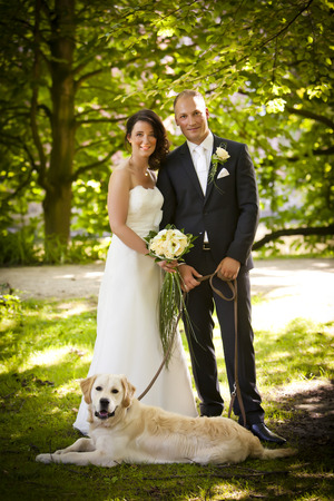 couple nature: newlywed couple with bouquet and dog after wedding