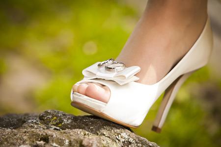 Salon de la mariée avec de beaux ongles et les orteils ouverts avec des anneaux sur elle