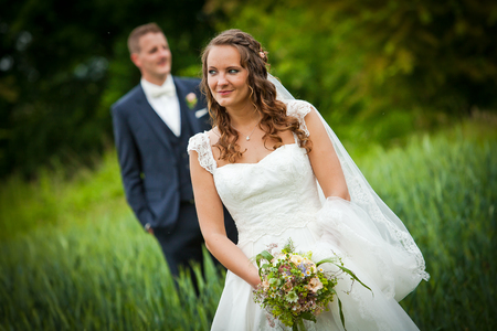 wedding couple - nice pretty bride is looking with handsome husband in background