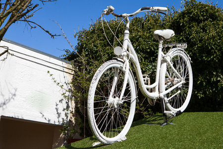 White bike as advertisement on a green grass meadow from a bicycle shop where you can rent a bike
