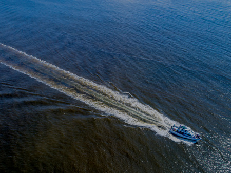 An aerial shot of a yacht out on a cruise, speeding toward home at the end of the day. Stock fotó