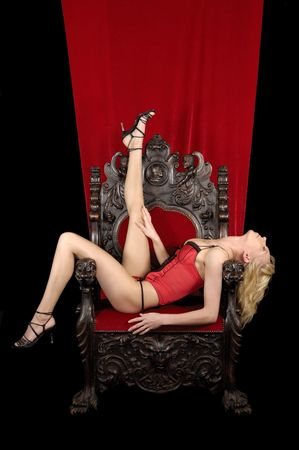 A sexy woman is sitting an a throne