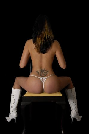 A sexy woman is sitting an a chair photo