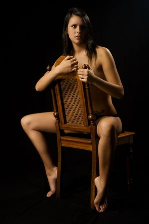 A sexy woman is sitting an a chair