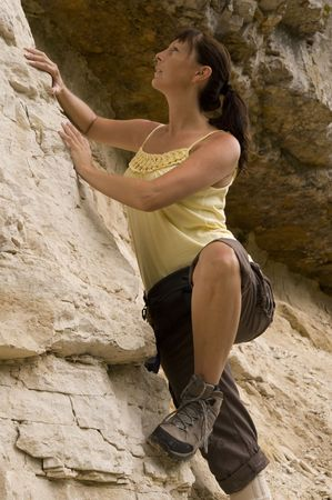 rockwall: a young woman is doing some freeclimbing at the rock-wall