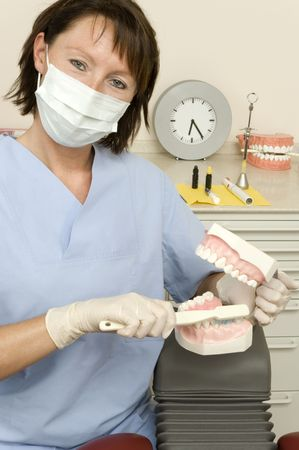 dentalcare: dentist shows how to use the teeth brush correctly Stock Photo