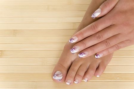manicure and pedicure: beautiful hand and foot with fresh manicured nails Stock Photo
