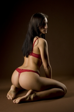 slip: woman in kneeling position in red lingerie over dark lighting Stock Photo