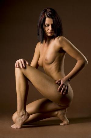 nude brunette model kneeling on the floor