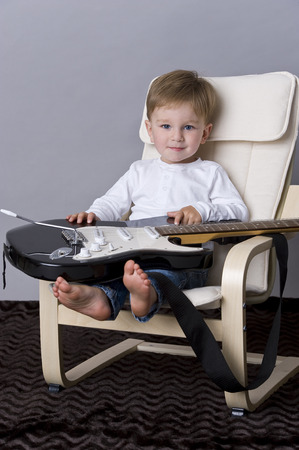 tiddler: Portrait of happy baby boy  and guitar on lab