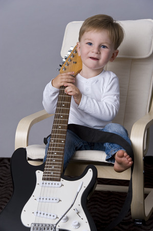 tiddler: Portrait of happy baby boy  holding a guitar