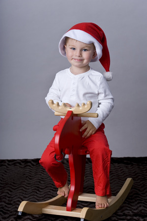 tiddler: Portrait of happy baby boy  sitting on wooden horse