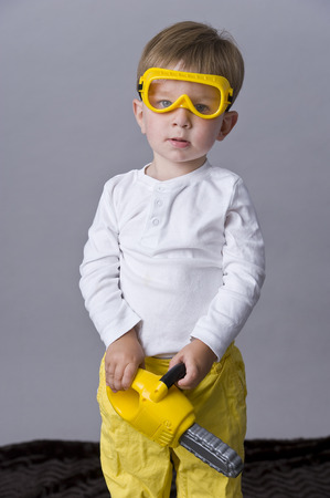 tiddler: Portrait of happy baby boy  holding a toy saw Stock Photo
