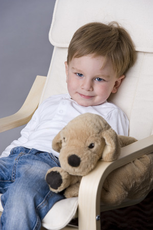 tiddler: Portrait of happy baby boy sitting on chair with his teddy bear
