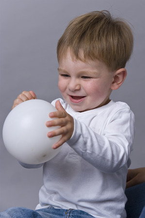 Portrait of happy baby boy playing with ball Stock Photo