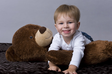 tiddler: Portrait of happy baby boy playing with his teddy bear