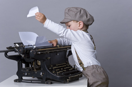 Portrait of happy baby boy playing with old typewriter