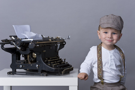 tiddler: Portrait of happy baby boy playing with old typewriter