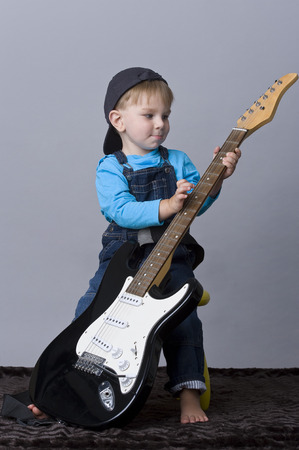 tiddler: Portrait of happy baby boy playing with guitar Stock Photo
