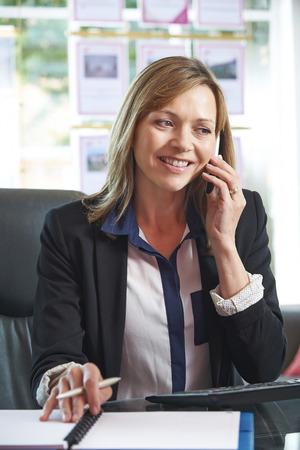 verticales: Agente de raíces en el teléfono en la oficina