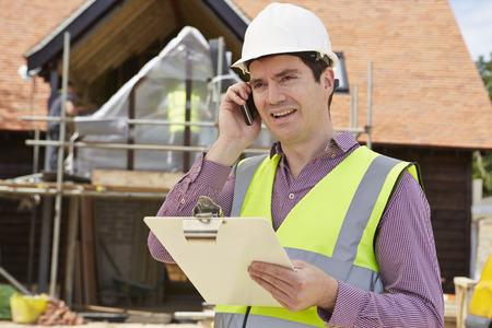 waistcoat: Architect On Building Site Using Mobile Phone Stock Photo